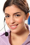 Telephone operator using headset smiling at camera Stock Image