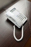 Telephone over brown desk Stock Image