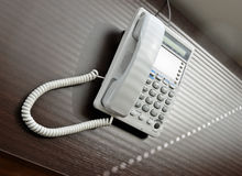 Telephone over brown desk Stock Images