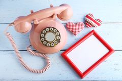 Telephone with photo frame and hearts. Pink retro telephone with photo frame and hearts on white wooden table stock photo