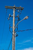 Telephone Pole With Street Lamp. A convoluted mess of wires and cables clutter a wooden telephone pole and street lamp royalty free stock photos