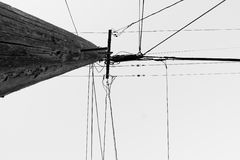 Telephone Pole and Wires. A telephone pole and wires against a white sky. Black and white image Royalty Free Stock Images