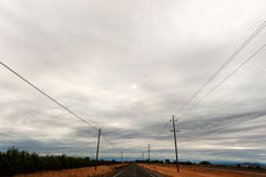 Telephone poles line a road in the country Stock Image
