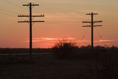 Telephone poles and sunset. On the great plains royalty free stock photography
