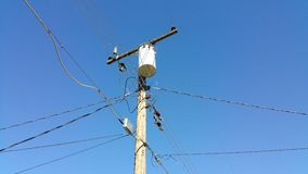 Telephone Poll With Cables. Cables coming out and going into a telephone poll against a blue sky Stock Photo