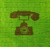 Telephone on puzzle texture. Abstract green background with brown telephone on puzzle texture Stock Photos
