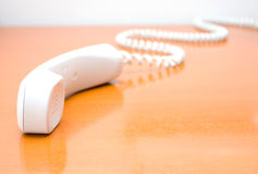 Telephone receiver. The white telephone receiver on table royalty free stock photo