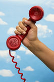 Telephone Receiver. Red telephone receiver on a hand on sky background Stock Photos