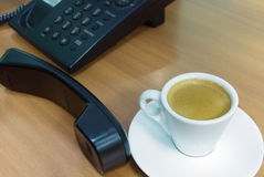 Telephone receiver and coffee. Black telephone receiver and cup of espresso Royalty Free Stock Images