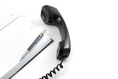 Telephone receiver and notebook Royalty Free Stock Images