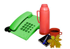 Telephone set. Telephone set green colour and a red thermos Royalty Free Stock Photos