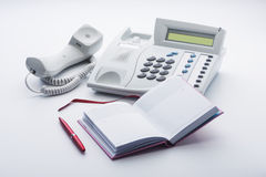 The telephone set, notepad and pen on a white background Stock Photography