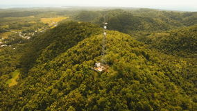 Telephone signal tower among green forest and mountains. Aerial view. Siargao island Philippines. Communication tower, cellphone tower in the jungle in the stock video