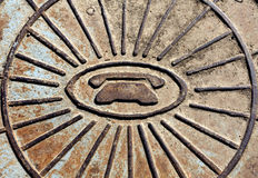 Telephone symbol icon on rusty manhole cover. Royalty Free Stock Images