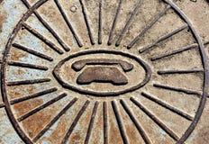 Telephone symbol icon on rusty manhole cover. Royalty Free Stock Images