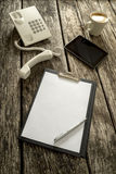 Telephone, Tablet, Coffee and Paper on Table Stock Images