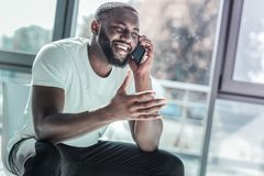 Positive delighted man talking per telephone. Telephone talk. Cheerful brunette smiling while actively gesticulating and sitting in office stock images