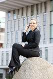 Telephoning businesswoman. Telephoning young businesswoman sitting in front of office Royalty Free Stock Photos