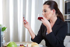 Telephoning woman. A telephoning woman with tea in kitchen Royalty Free Stock Image