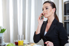 Telephoning woman. A telephoning woman with tea in kitchen Stock Image