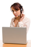 Telephonist on a company help desk. Attractive young telephonist on a company help desk sitting behind her laptop computer listening to a call Stock Image