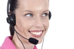 Close up female telephonist with telephone headset smiling, looking away from camera. Beautiful female telephone worker with headset and lovely smile Royalty Free Stock Image