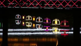 Telephoto medium shot of colorful glowing buoys on a reflecting river in Asia variation stock video footage
