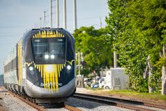 Telephoto shot of the Brightline train on tracks. Hollywood, FL, USA - May 25, 2019: Telephoto shot of the Brightline train on tracks stock image