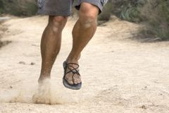 Running wild in primitive sandals. Telephoto shot legs of rugged male runner in shorts and primitive sandals running hard on dirt trail Royalty Free Stock Image
