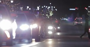 Telephoto View Holiday Traffic with People at Night. Low angle telephoto view of heavy traffic with people crossing the street during the holidays on a cold stock video footage