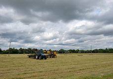 Pair of agriculture vehicles seen collecting bales of straw on an arable field. The teleport can be seen loading large bales onto the back of a tractor trailer Stock Photos