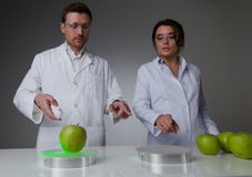 Teleportation or cloning concept. Two scientists in laboratory doing futuristic research experiments with apples, teleportation or cloning concept Royalty Free Stock Image