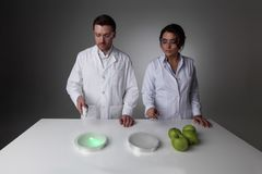 Teleportation or cloning concept. Two scientists in laboratory doing futuristic research experiments with apples, teleportation or cloning concept stock images