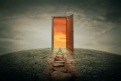 Teleportation door. Pathway along a dry, cracked desert land, going to a opened door to another better and colorful world. Road of opportunity and success symbol Royalty Free Stock Photos