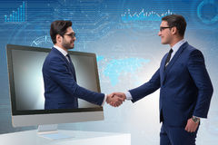 The telepresence concept with two businessman handshaking Stock Photos