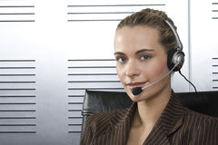 Telesales blond. Young blond call center agent talking on the headset in a modern office setting Royalty Free Stock Photo
