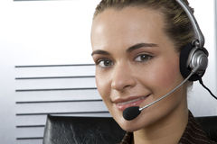 Telesales blond. Young blond call center agent talking on the headset in a modern office setting Stock Photo