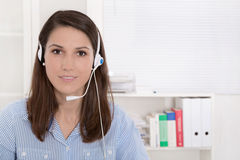 Telesales or helpdesk - helpful woman with headset smiling at ca Royalty Free Stock Photography