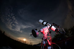 Telescope. The telescope is pointed at the sky. The rising moon and stars stock image