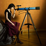 Telescope. Young beautiful girl sitting on the bed looking to the telescope stock images