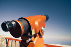 Telescope against blue sky background Stock Photos