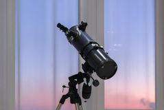 Telescope in the background of a window. With a pink and purple sunset Royalty Free Stock Images