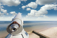 Telescope on a beach pointed at beautiful sky Stock Image
