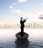 Telescope and city. Businessman looking through a telescope and city royalty free stock photo