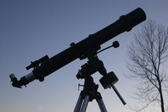 Telescope at Dusk. Semi-silhouette view of a four-inch refractor telescope at dusk Stock Images
