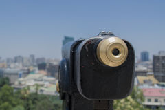 A telescope looking to the city. Close up of a telescope with an unfocused view of the city stock photos