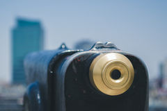 A telescope looking to the city. Close up of a telescope with an unfocused view of the city royalty free stock image