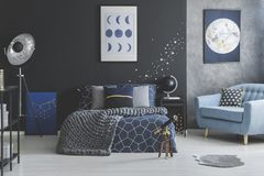 Star stickers in blue bedroom. Telescope near bed with knit blanket against dark wall with star stickers in blue bedroom interior royalty free stock photography