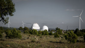 A telescope observatory dome and windmills Royalty Free Stock Photos