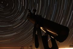 Observing the North Star. A telescope points off toward the North Star during a long exposure photograph partially illuminated by a passing car stock photo